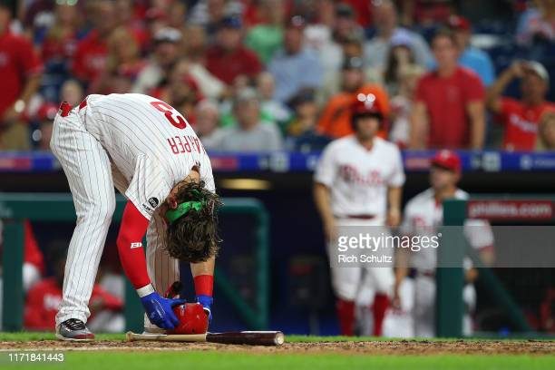 Bryce Harper of the Philadelphia Phillies reacts after being hit in the back by a pitch from Jose Quijada of the Miami Marlins during the fourth...