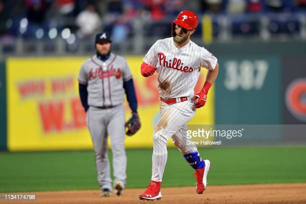 Bryce Harper of the Philadelphia Phillies rounds the bases in front of Josh Donaldson of the Atlanta Braves after hitting a home run in the seventh...