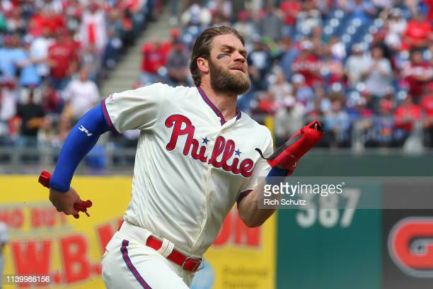 Bryce Harper of the Philadelphia Phillies rounds third base as he scores on a double by Rhys Hoskins against the Miami Marlins during the first...