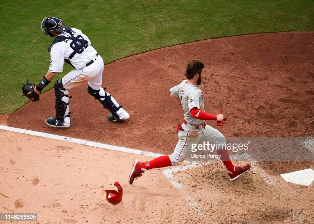 Bryce Harper of the Philadelphia Phillies scores ahead of the throw to Austin Allen of the San Diego Padres during the seventh inning of a baseball...