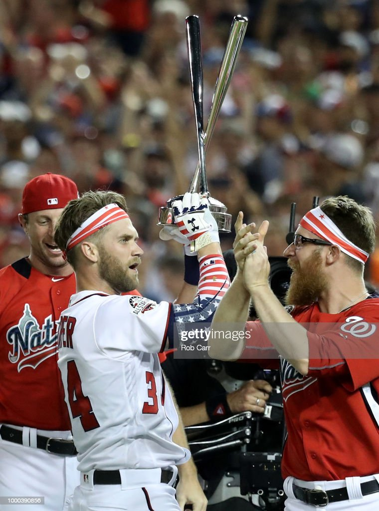 Bryce Harper of the Washington Nationals and National League celebrates with the trophy and teammates Max Scherzer #31 and Sean Doolittle #62 after winning the T-Mobile Home Run Derby at Nationals Park on July 16, 2018 in Washington, DC.