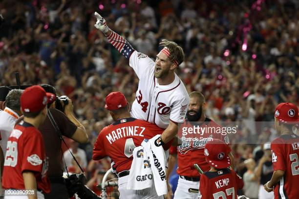 Bryce Harper of the Washington Nationals and National League celebrates with his manager Dave Martinez and father Ron Harper after winning the...