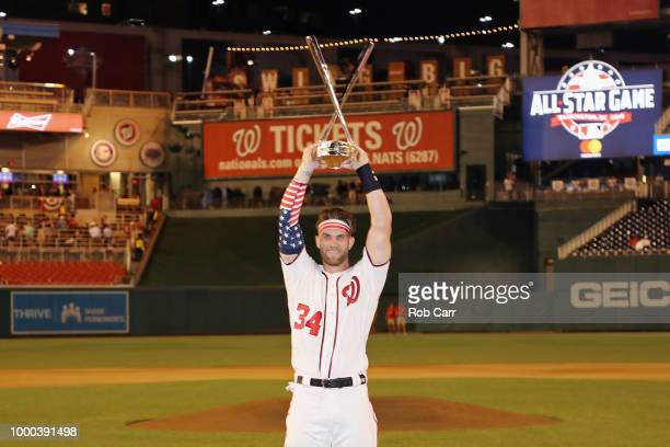 Bryce Harper of the Washington Nationals and National League celebrates with the trophy after winning the TMobile Home Run Derby at Nationals Park on...