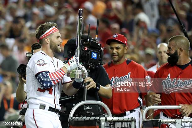 Bryce Harper of the Washington Nationals and National League celebrates with the trophy and manager Dave Martinez as his father Ron Harper looks on...