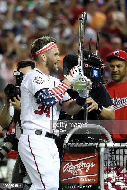 Bryce Harper of the Washington Nationals and National League celebrates with the trophy and manager Dave Martinez after winning the TMobile Home Run...