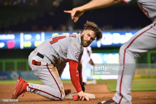 Bryce Harper of the Washington Nationals at lands at third base in the sixth inning against the Miami Marlins at Marlins Park on September 18 2018 in...