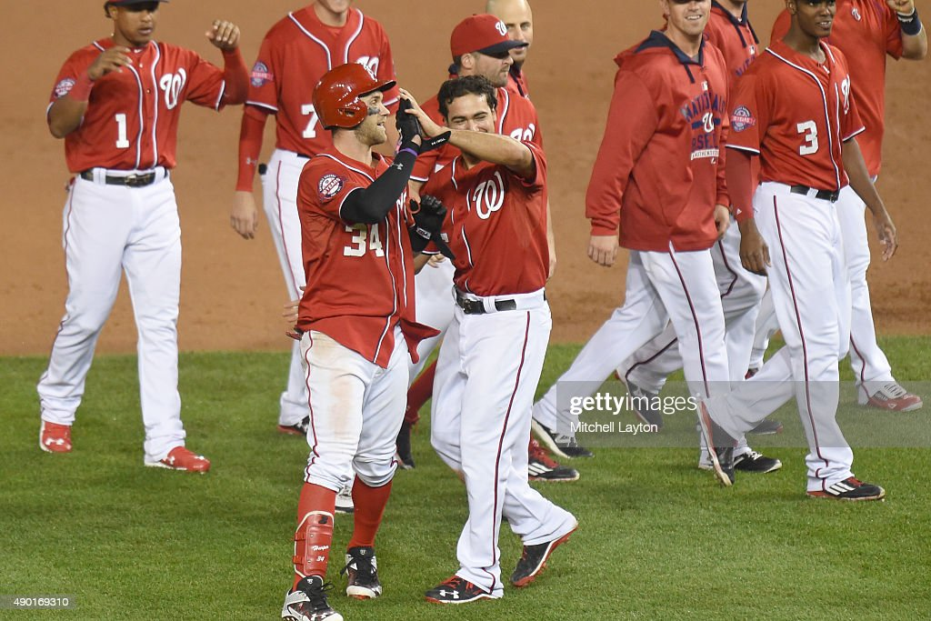 Bryce Harper #34 of the Washington Nationals celebrates a walk off double in the 12th inning with Anthony Rendon #6 after a baseball game against the Philadelphia Phillies at Nationals Park on September 26, 2015 in Washington, DC. The Nationals won 2-1 in the 12th inning.