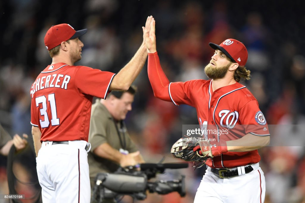 Bryce Harper #34 of the Washington Nationals celebrates a win with Max Scherzer #31 after game two of a doubleheader against the Colorado Rockies at Nationals Park on July 30, 2017 in Washington, DC.