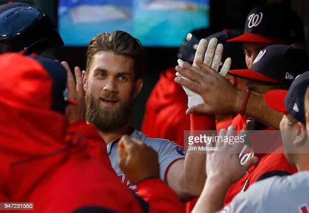 Bryce Harper of the Washington Nationals celebrates his first inning home run against the New York Mets with his teammates in the dugout at Citi...