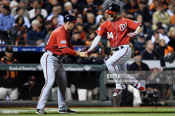 Bryce Harper of the Washington Nationals celebrates his solo home run with third base coach Bob Henley in the seventh inning against the San...