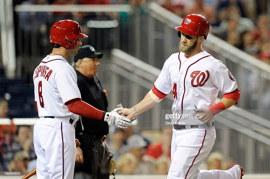 Bryce Harper #34 of the Washington Nationals celebrates with Danny Espinosa #8 after scoring in the third inning against the Chicago White Sox at Nationals Park on April 11, 2013 in Washington, DC.