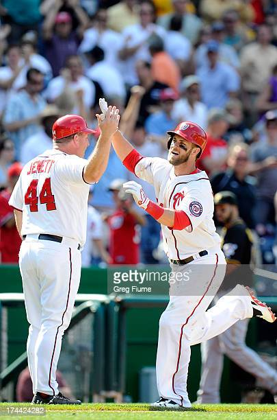 Bryce Harper of the Washington Nationals celebrates with third base coach Trent Jewett after hitting the game winning home run in the ninth inning...