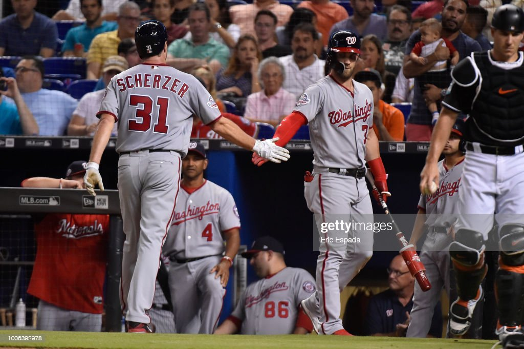 Bryce Harper #34 of the Washington Nationals congratulates Max Scherzer #31 after scoring on a wild pitch during the third inning against the Miami Marlins at Marlins Park on July 27, 2018 in Miami, Florida.