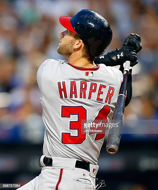Bryce Harper of the Washington Nationals follows through on a first inning run scoring sacrifice fly against the New York Mets at Citi Field on...