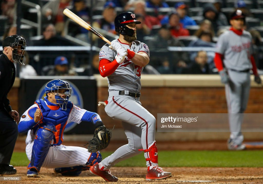 Bryce Harper #34 of the Washington Nationals follows through on an eighth inning two run single against the New York Mets at Citi Field on April 16, 2018 in the Flushing neighborhood of the Queens borough of New York City.