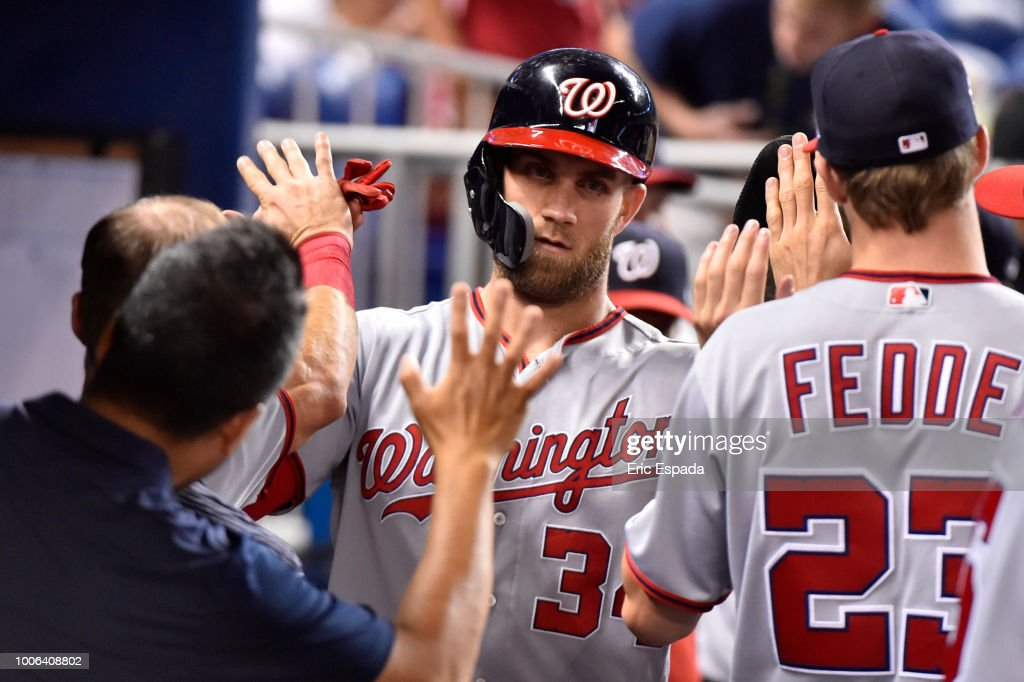 Bryce Harper #34 of the Washington Nationals is congratulated by teammates after scoring in the eighth inning against the Miami Marlins at Marlins Park on July 27, 2018 in Miami, Florida.