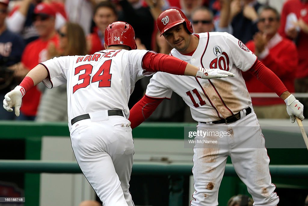 Bryce Harper #34 of the Washington Nationals is congratulated by Ryan Zimmerman #11 after hitting a solo home run in the bottom of the first inning during the Opening Day game against the Miami Marlins at Nationals Park on April 1, 2013 in Washington, DC.