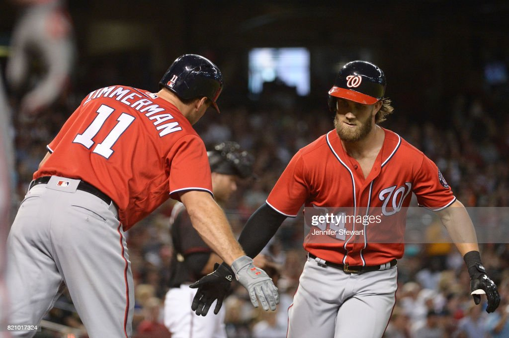 Bryce Harper #34 of the Washington Nationals is congratulated by Ryan Zimmerman #11 after hitting a solo homer during the first inning of the MLB game against the Arizona Diamondbacks at Chase Field on July 22, 2017 in Phoenix, Arizona.
