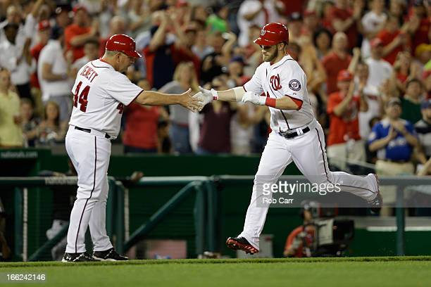 Bryce Harper of the Washington Nationals is congratulated by third base coach Trent Jewett after hitting a solo home run against the Chicago White...