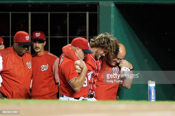 Bryce Harper of the Washington Nationals is helped into the locker room after injuring his leg in the first inning against the San Francisco Giants...