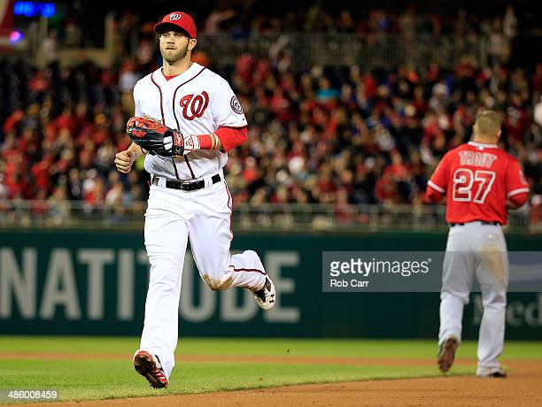 Bryce Harper of the Washington Nationals jogs past Mike Trout of the Los Angeles Angels after Trout lined out for the third out of the seventh inning...