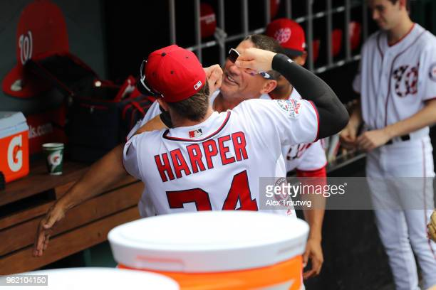 Bryce Harper of the Washington Nationals jokes with first base coach Tim Bogar in the dugout before the start of a game against the San Diego Padres...