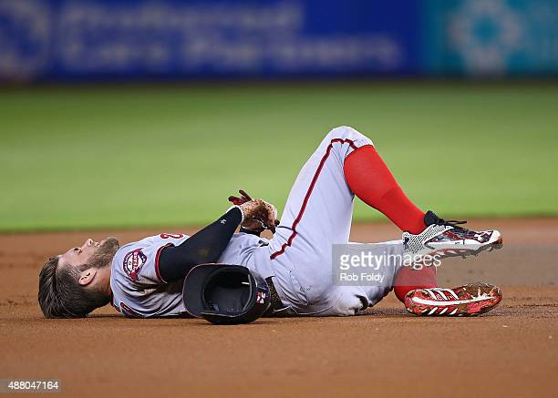 Bryce Harper of the Washington Nationals lays injured on the infield after colliding with Miguel Rojas of the Miami Marlins during the first inning...