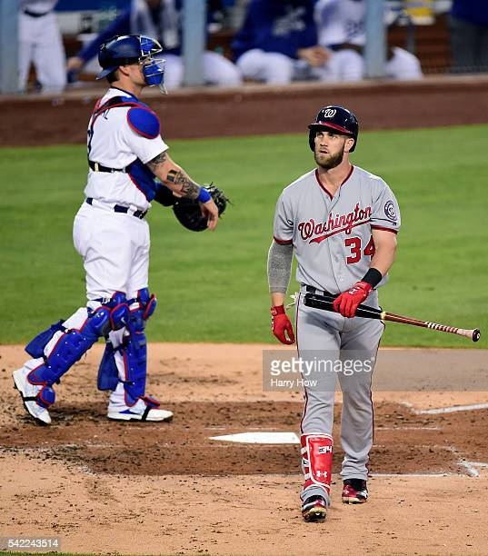 Bryce Harper of the Washington Nationals reacts to his strikeout in front of Yasmani Grandal of the Los Angeles Dodgers during the third inning at...