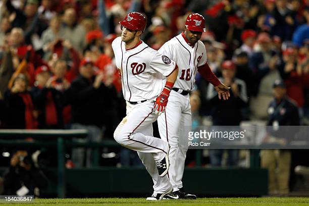 Bryce Harper of the Washington Nationals rounds the bases and is congratulated by third base coach Bo Porter after Harper hits a home run in the...