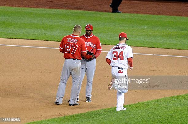 Bryce Harper of the Washington Nationals runs by Mike Trout of the Los Angeles Angels between innings of the game at Nationals Park on April 23 2014...