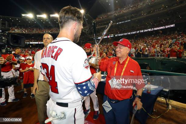 Bryce Harper of the Washington Nationals shares the home run derby trophy with Nationals owner Mark Lerner after winning the TMobile Home Run Derby...