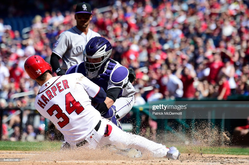 Bryce Harper #34 of the Washington Nationals slides in safely to score ahead of the tag by catcher Tony Wolters #14 of the Colorado Rockies in the sixth inning at Nationals Park on April 14, 2018 in Washington, DC.