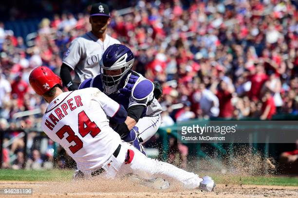 Bryce Harper of the Washington Nationals slides in safely to score ahead of the tag by catcher Tony Wolters of the Colorado Rockies in the sixth...