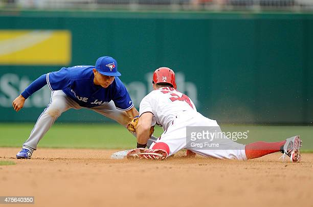 Bryce Harper of the Washington Nationals steals second base in the seventh inning ahead of the tag by Munenori Kawasaki of the Toronto Blue Jays at...