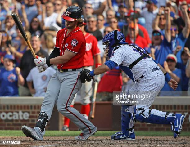 Bryce Harper of the Washington Nationals strikes out and is tagged by Alex Avila of the Chicago Cubs to end the game at Wrigley Field on August 5...