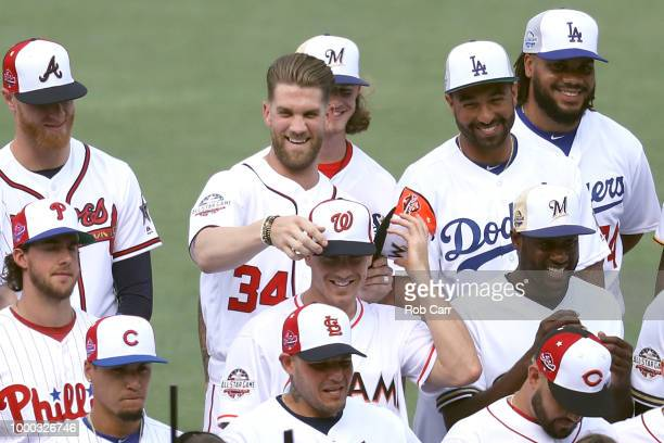 Bryce Harper of the Washington Nationals switches hats with JT Realmuto of the Miami Marlins during the National League AllStar team photo during...