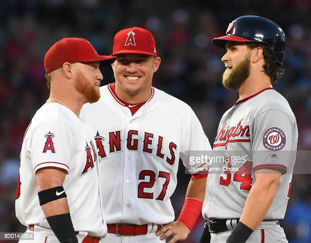 Bryce Harper of the Washington Nationals talks with Kole Calhoun and Mike Trout of the Los Angeles Angels as a play if being reviewed in the game at...