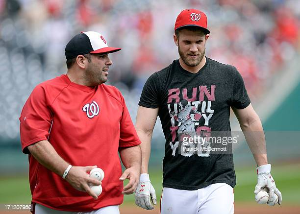 Bryce Harper of the Washington Nationals talks with Nationals batting practice pitcher Ali Modami before a game between the Nationals and Colorado...