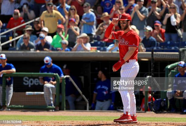 Bryce Harper scores on a two run home run in the first inning by Rhys Hoskins of the Philadelphia Phillies during a game against the Toronto Blue...