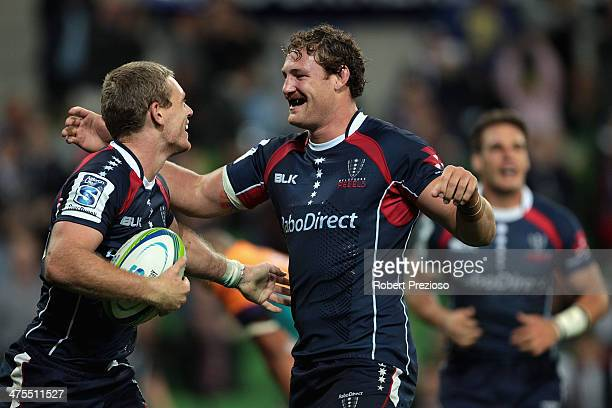 Bryce Hegarty of the Rebels celebrates with teammate Scott Higginbotham of the Rebels after crossing the line to score a try during the round three...