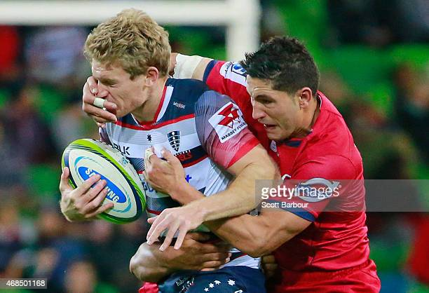 Bryce Hegarty of the Rebels is tackled by Anthony Faingaa of the Reds during the round eight Super Rugby match between the Rebels and the Reds at...