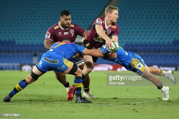 Bryce Hegarty of the Reds passes while tackled during the round eight Super Rugby AU match between the Western Force and the Queensland Reds at Cbus...