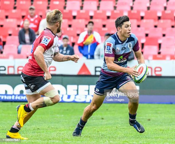 Bryce Hegarty of the Reds with possession challenged by Tyrone Green of the Lions during the Super Rugby match between Emirates Lions and Reds at...