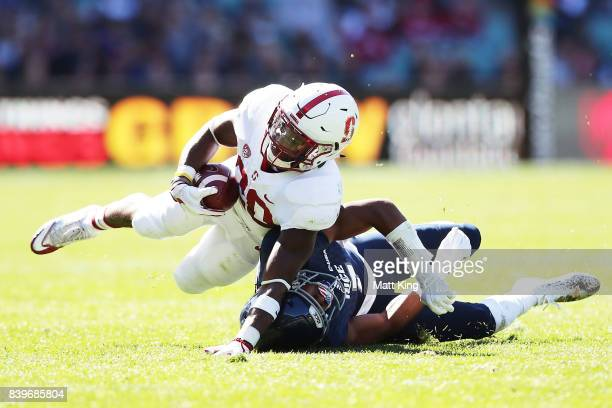 Bryce Love of Stanford is tackled by Justin Bickham of Rice during the College Football Sydney Cup match between Stanford University and Rice...