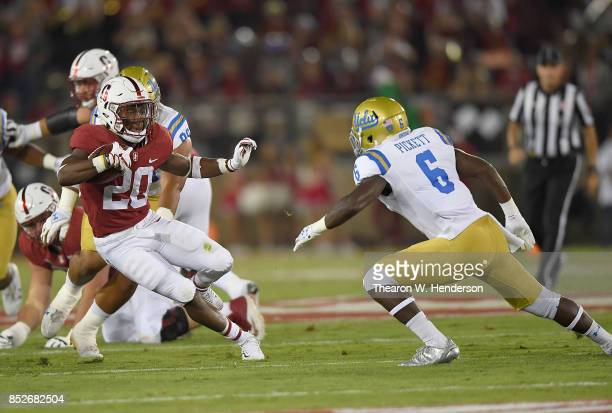 Bryce Love of the Stanford Cardinal carries the ball while looking to avoid the tackle of Adarius Pickett of the UCLA Bruins during the first quarter...