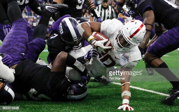 Bryce Love of the Stanford Cardinal is tackled in the second half by Corey Bethley of the TCU Horned Frogs and Arico Evans of the Valero Alamo Bowl...