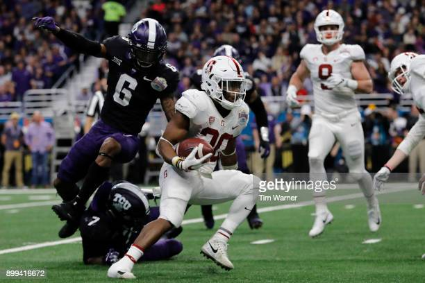 Bryce Love of the Stanford Cardinal runs past Innis Gaines of the TCU Horned Frogs and Arico Evans in the second quarter during the Valero Alamo Bowl...