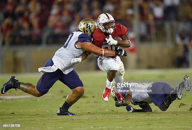 Bryce Love of the Stanford Cardinal's gets tackled by Taniela Tupou of the Washington Huskies in the firs quarter of an NCAA football game at...