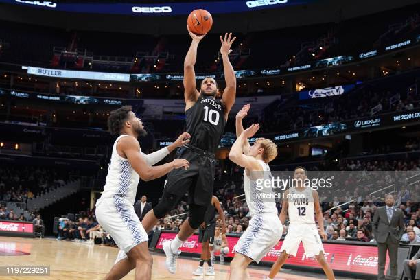 Bryce Nze of the Butler Bulldogs drives to the basket between Jagan Mosely and Mac McClung of the Georgetown Hoyas in the second half during a...