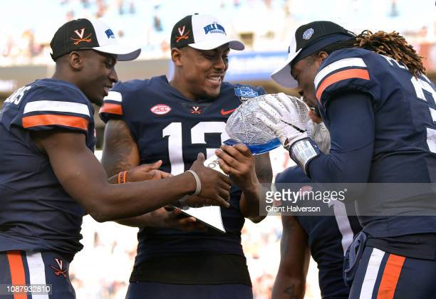 Bryce Perkins of the Virginia Cavaliers kisses the trophy after a win against the South Carolina Gamecocks during the Belk Bowl at Bank of America...